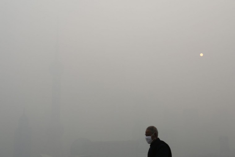 A man wears a face mask while walking on the Bund in front of the financial district of Pudong during a hazy day in downtown Shanghai December 6, 2013. China's stability-obsessed leadership has become increasingly concerned by the abysmal air quality in cities, as it plays into popular resentment over political privilege and rising inequality in the world's second-largest economy. (REUTERS/Aly Song)