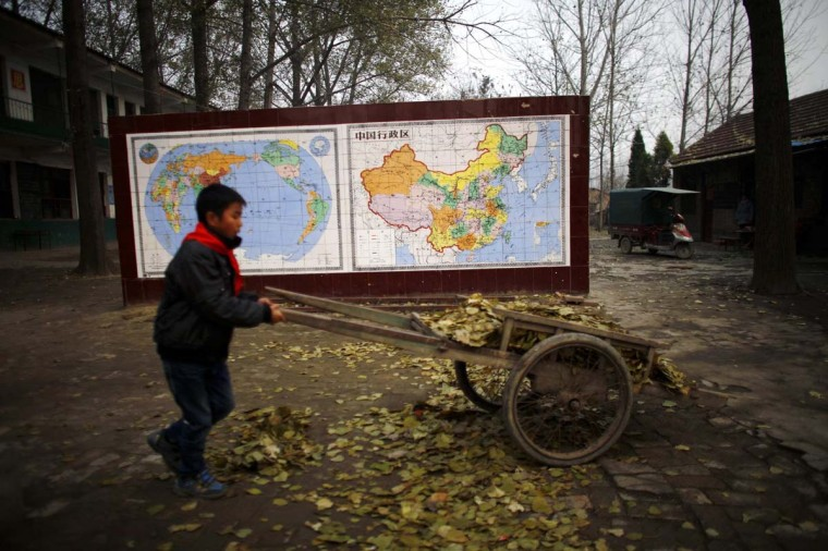 A student collects leaves at the Democracy Elementary and Middle School in Sitong town, Henan province December 3, 2013. In a remote part of central China, the day starts at the Democracy Elementary and Middle School with a pre-dawn jog, some revolutionary songs and then an activity long since forgotten at other schools: reciting quotations from Mao Zedong's famed 'Little Red Book'. While the ruling Communist Party that Mao led continues to hold him in esteem as the leader of the Communist Revolution, his radical policies and teachings have been largely shelved since his death in 1976 in favour of a pro-market approach that has turned China from a backwater into the world's second biggest economy. The 120th anniversary of Mao's birth is on December 26, 2013. Picture taken December 3, 2013. REUTERS/Carlos Barria