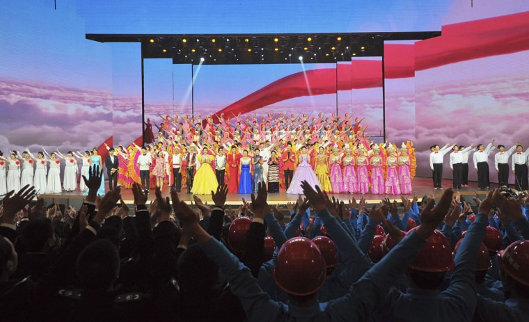 Audiences (bottom) raise their hands as performers sing a song at the end of a performance to celebrate the upcoming 120th anniversary of the birthday of Chinese late Chairman Mao Zedong, in Changsha, Hunan province December 23, 2013. Thursday, December 26, 2013, marks the 120th anniversary of Mao's birth, while various commemorative activities are scheduled to carry out in Hunan province, where Mao was born, and throughout the nation. Picture taken December 23, 2013. (REUTERS/China Daily)