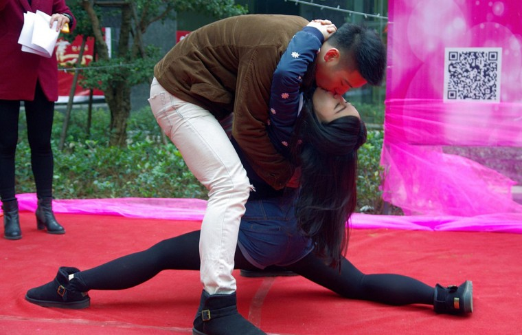 A couple participates in a kissing competition to celebrate Christmas in Wuhan, Hubei province. The competition required the attendants to kiss in different postures for a prize worth 15,000 Yuan ($2,470), local media reported. Picture taken December 24, 2013. (Stringer/Reuters)