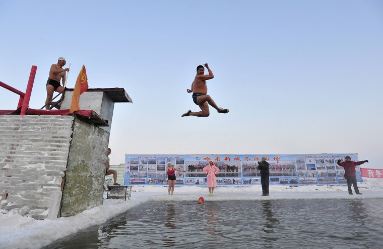 A winter swimmer gestures as he jumps into the icy water of partially frozen Songhua River in Harbin, Heilongjiang province December 28, 2013. The temperature in Harbin on Saturday reached as low as minus 21 degrees Celsius (minus 5.8 degrees Fahrenheit). (REUTERS/Sheng Li)