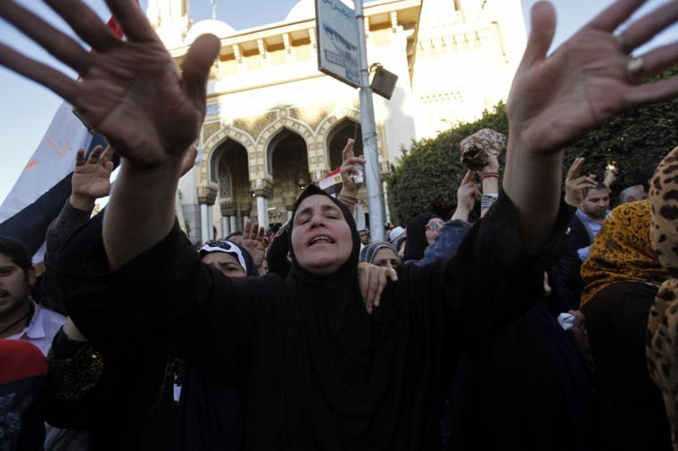 """A woman cries during a funeral service for policemen and people killed in a car bomb explosion, near Al Naser Mosque in Egypt's Nile Delta city of Mansoura in Dakahlyia province, about 120 km (75 miles) northeast of Cairo, December 24, 2013. The car bomb tore through a police compound in Mansoura on Tuesday, killing 13 people and wounding more than 130, security officials said, in one of the deadliest attacks since the army deposed Islamist President Mohamed Mursi in July. The army-backed government vowed to fight """"black terrorism"""", saying the blast an hour after midnight in the city of Mansoura north of Cairo would not derail a political transition plan whose next step is a January referendum on a new constitution. (REUTERS/Mohamed Abd El Ghany)"""