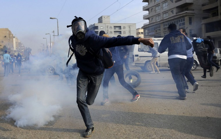 A supporter of ousted President Mohamed Mursi throws a tear gas canister back towards police during clashes at Nasr City district in Cairo December 20, 2013. (REUTERS/ Mohamed Abd El Ghany )