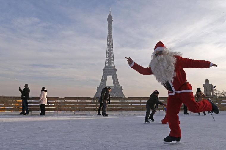 A man dressed as Santa Claus skates on an ice rink across from the Eiffel Tower as part of the Christmas holiday season preparations, in Paris December 12, 2013. (REUTERS/Jacky Naegelen)