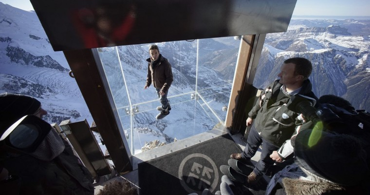Journalists and employees, wearing slippers to protect the glass floor, visit the 'Step into the Void' installation. The Chamonix Skywalk is a five-sided glass structure installed on the top terrace of the Aiguille du Midi (3842m), with a 1,000 meter drop below, where visitors can step out from the terrace, giving the visitors the impression of standing in the void. The glass room will open to the public on December 21, 2013. (REUTERS / Robert Pratta)