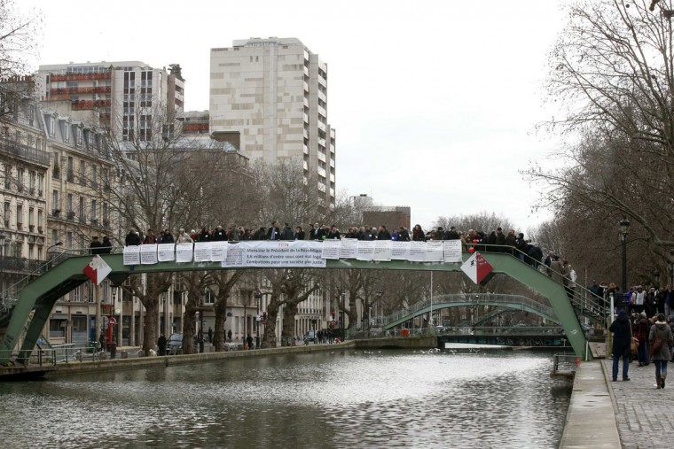 "The group ""Collectif of 34 United Associations"" gather to ask for new housing policy for homeless people as they wish a happy new year to the French president and to the nation during a news conference at the Canal Saint Martin in Paris, December 31, 2013. Seven years ago, at the same place the French association ""Les Enfants de Don Quichotte"" (Children of Don Quichotte) was setting up tents for the homeless. (REUTERS/Benoit Tessier)"