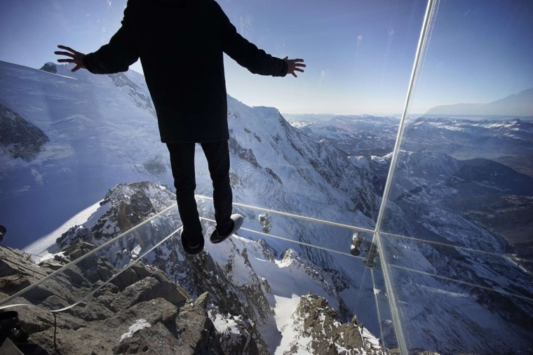 A journalist, wearing slippers to protect the glass floor, stands in the 'Step into the Void' installation. The Chamonix Skywalk is a five-sided glass structure installed on the top terrace of the Aiguille du Midi (3842m), with a 1,000 meter drop below, where visitors can step out from the terrace, giving the visitors the impression of standing in the void. The glass room will open to the public on December 21, 2013. (REUTERS / Robert Pratta)
