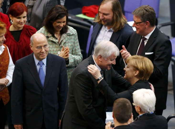 "German Chancellor Angela Merkel is congratulated by Horst Seehofer (C) of the Christian Social Union (CSU) after being re-elected as chancellor during a meeting of the Bundestag, the lower house of parliament in Berlin December 17, 2013. Merkel was elected to a third term as chancellor in a vote in the German lower house of parliament on Tuesday, paving the way for her new ""grand coalition"" government to be sworn in and formally take power later in the day. (Tobias Schwarz/Reuters)"