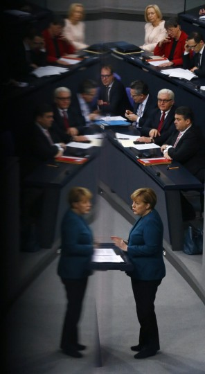 German Chancellor Angela Merkel is reflected in a glass barrier as she addresses the German lower house of parliament, Bundestag in Berlin. (Tobias Schwarz/Reuters)
