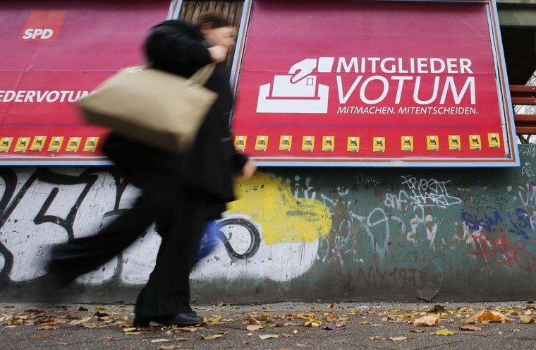 "A pedestrian walks past an advertisement reading ""Member Vote"" to promote the voting for a coalition between the Social Democratic Party (SPD) and the Christian Democratic Union (CDU) in Berlin. SPD leader Sigmar Gabriel has urged the party's 474,000 members to vote for a coalition agreement. The results of the ballot will be known on December 14. REUTERS/Fabrizio Bensch"