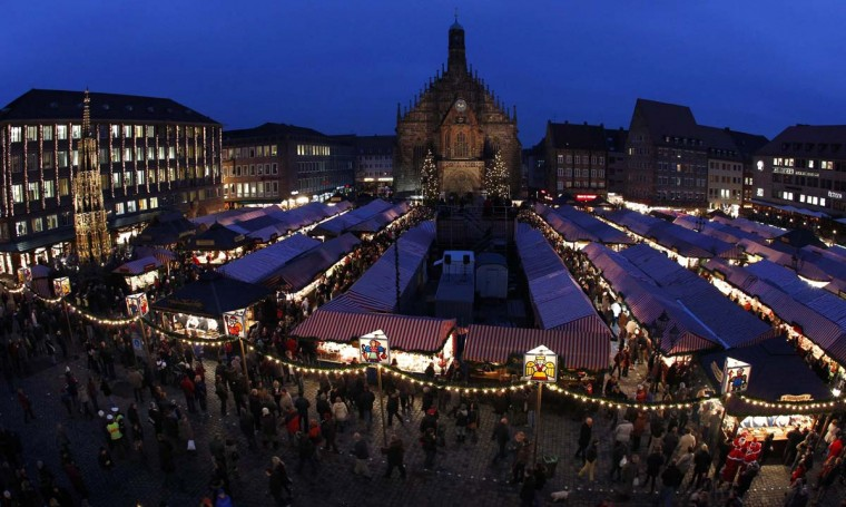 People visit Germany's oldest Christkindlesmarkt (Christ Child Market) on its opening day in Nuremberg November 29, 2013. The first official record of this pre-Christmas market dates back to 1628. A list of notices for stall holders from 1737 shows that almost all of Nuremberg's craftsmen were represented. Every year, Germany's traditional markets, such as the centuries-old Christkindlesmarkt in medieval Nuremberg, draw millions of visitors, both local and foreign. They open before the first Sunday of Advent and usually continue until December 24 at 12 noon. (REUTERS/Michaela Rehle)