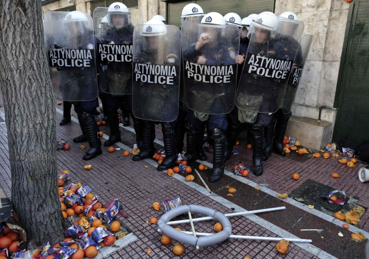 Policemen take cover as farmers throw oranges at them during a rally against the government's new property tax outside the parliament in Athens December 20, 2013. (REUTERS/John Kolesidis)