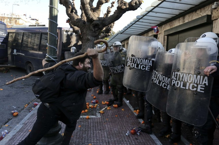 A farmer uses a stick to hit policemen during a rally against the government's new property tax outside the parliament in Athens December 20, 2013. (REUTERS/John Kolesidis)