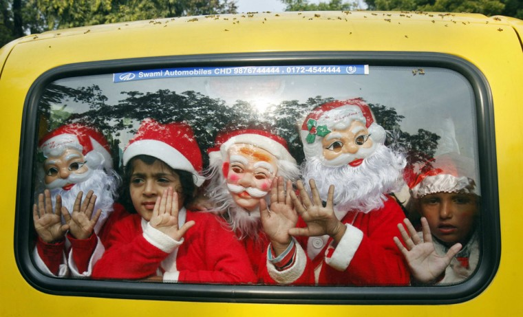 Children dressed in Santa Claus costumes wave as they travel in a vehicle after attending Christmas celebrations at a church in the northern Indian city of Chandigarh December 23, 2013. (Ajay Verma/Reuters)