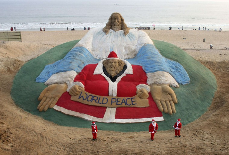 Children dressed in Santa Claus costumes pose in front of a sand sculpture featuring Jesus Christ (top) and Santa Claus created by Indian artist Sudarshan Pattnaik as part of Christmas celebrations on a beach in Puri, located in the eastern Indian state of Odisha, December 24, 2013. (REUTERS)