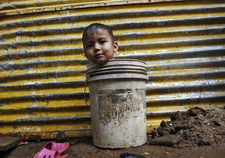 A boy sits in a bucket as he plays while waiting for his mother to fetch water from a nearby hand pump to bathe him, outside a makeshift hut in the southern Indian city of Chennai December 30, 2013. (Babu/Reuters)