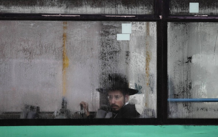 An ultra-Orthodox Jewish man looks out from a condensation-covered window of a bus in Jerusalem. High winds and heavy rain showers poured across Israel on Wednesday with local media reporting by mid-morning 45 mm of rain in a central town near Tel Aviv, and snow had covered Mount Hermon near Israel's border with Syria. (Ammar Awad/Reuters)