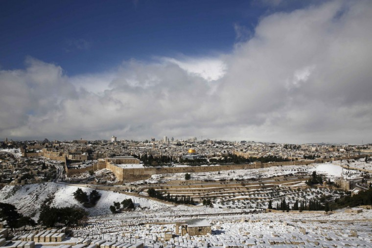 A view of Jerusalem's Old City following a snowstorm is seen from the Mount of Olives December 13, 2013. A snowstorm of rare intensity blanketed the Jerusalem area and parts of the occupied West Bank on Friday, choking off the city and stranding hundreds in vehicles on impassable roads. (REUTERS/Darren Whiteside)