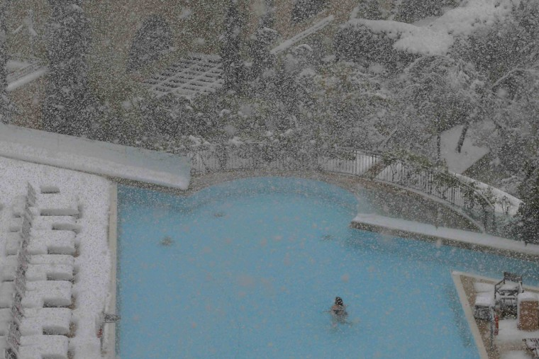 A woman swims in the pool at the David Citadel Hotel during a snow storm in Jerusalem December 13, 2013. A snowstorm of rare intensity blanketed the Jerusalem area and parts of the occupied West Bank on Friday, choking off the city and stranding hundreds in vehicles on impassable roads. (REUTERS/Brian Snyder)