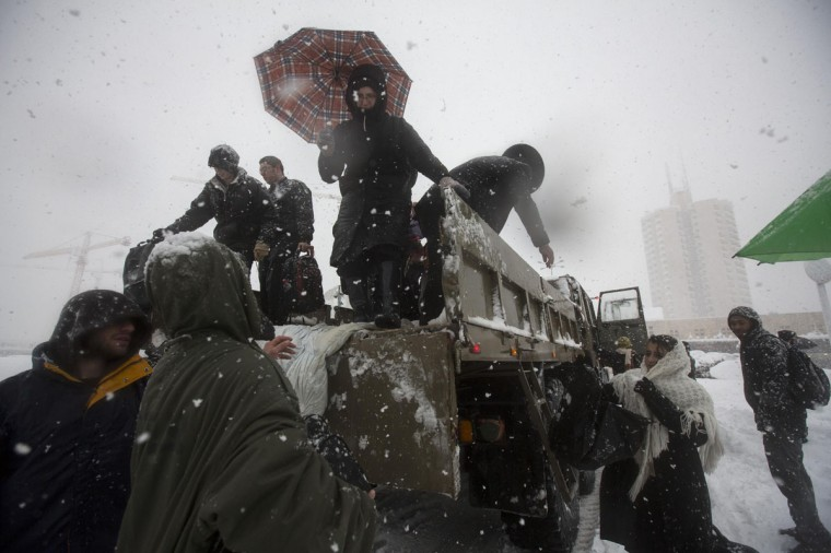 Israeli soldiers help stranded passengers off of an army truck to a temporary shelter after they had to leave their vehicles because of heavy snowfall in Jerusalem December 13, 2013. A snowstorm of rare intensity blanketed the Jerusalem area and parts of the occupied West Bank on Friday, choking off the city and stranding hundreds in vehicles on impassable roads. (REUTERS/Baz Ratner)