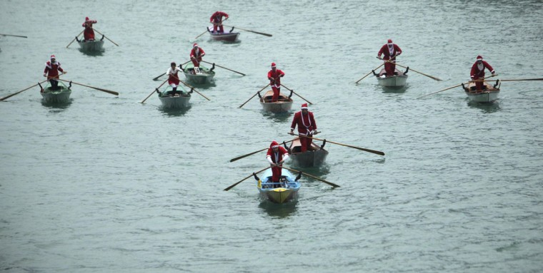 People dressed in Santa Claus costumes row boats on the Venice canal December 21, 2013. (REUTERS/Manuel Silvestri )