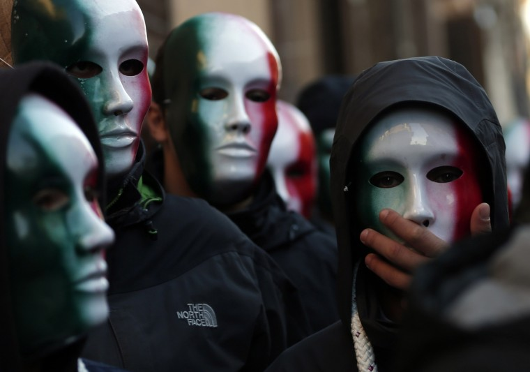 """Members of Casapound far-right organization wear masks in the colors of the Italian flag before a demonstration organized by """"People from pitchfork movement"""" to protest against economic insecurity and the government in downtown Rome December 18, 2013. Italy's """"pitchfork"""" protests spread to Rome on Thursday when hundreds of students clashed with police and threw firecrackers outside a university where government ministers were attending a conference. (Yara Nardi/Reuters)"""