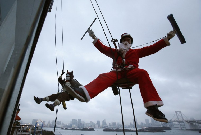 Window cleaners dressed as Santa Claus and a reindeer pose for photographers during an event to celebrate Christmas at a shopping mall in Tokyo December 19, 2013. (REUTERS/Yuya Shino)