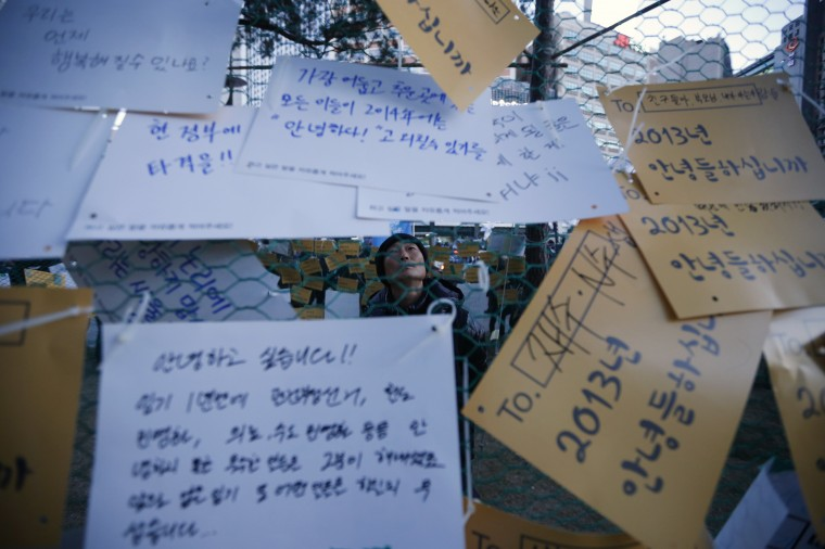 A South Korean worker looks at messages displaying requests for the government during a general strike in front of Seoul City Hall Plaza in Seoul December 28, 2013. About 30,000 South Korean workers attend the rally against government decision to set up a unit to run a high-speed bullet train which they say will lead to privatisation and layoffs. (REUTERS/Kim Hong-Ji)