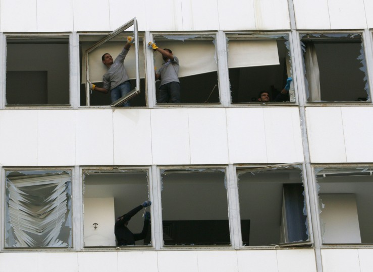 "Workers repair damaged windows at the Starco building in front of the site of a bomb blast, which killed Lebanon's former Finance Minister Mohamad Chatah, in downtown Beirut December 28, 2013. Chatah, who opposed Syrian President Bashar al-Assad, was killed in a massive bomb blast on Friday which one of his political allies blamed on the Shi'ite Hezbollah militia. Former prime minister Saad al-Hariri accused Hezbollah of involvement in the killing of Chatah, his 62-year-old political adviser, saying it was ""a new message of terrorism"". (REUTERS/Jamal Saidi )"