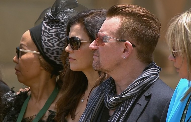 Musician Bono (2nd R) stands between his wife Ali Hewson (2nd L) and Zelda La Grange (R), former assistant of former South African President Nelson Mandela, during a visit to view Mandela's coffin as the anti-apartheid hero lies in state at the Union Buildings in Pretoria in this still image taken from video. (South Africa Broadcasting Corporation (SABC)/Reuters)