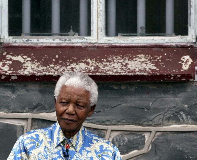 Former South African President Nelson Mandela sits beneath the window of his prison cell on Robben Island near Cape Town, in this November 28, 2003 file photo. Mandela has passed away on December 5, 2013 at the age of 95. (Mike Hutchings/REUTERS)