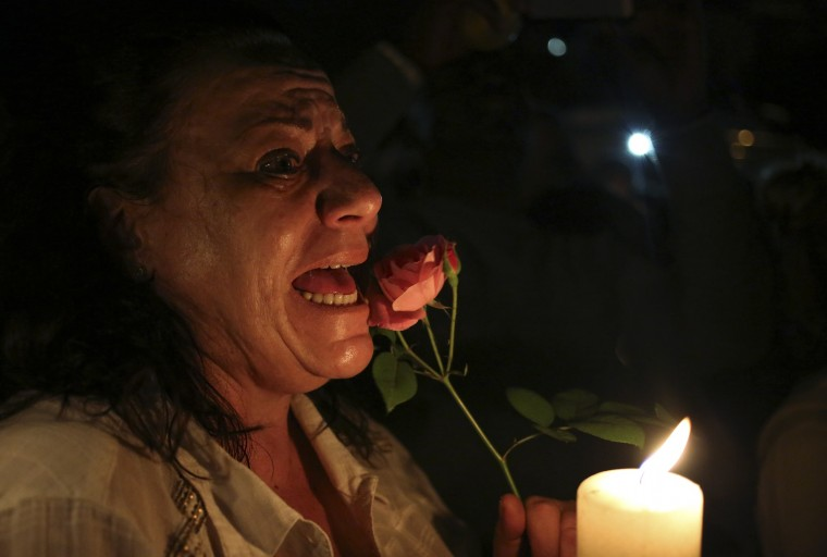 A women cries as she holds a candle and a flower outside former South African President Nelson Mandela's house in Houghton, December 5, 2013. Mandela died peacefully at his Johannesburg home on Thursday after a prolonged lung infection, President Jacob Zuma said. Mandela, the country's first black president and anti-apartheid icon known in South Africa by his clan name of Madiba, emerged from 27 years in apartheid prisons to help guide South Africa through bloodshed and turmoil to democracy. (Siphiwe Sibeko/REUTERS)