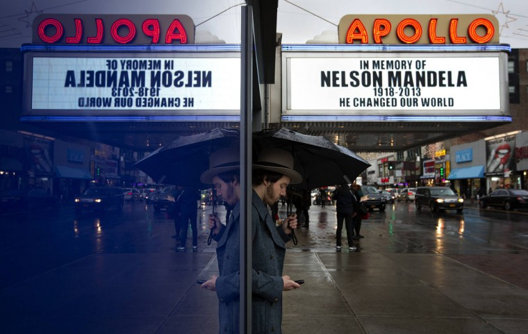A man is reflected in a window outside the Apollo Theatre as the marquee displays a memoriam to the late Nelson Mandela in the Harlem area of New York December 6, 2013. South African anti-apartheid hero Mandela died aged 95 at his Johannesburg home on Thursday after a prolonged lung infection, plunging his nation and the world into mourning for a man hailed by global leaders as a moral giant. (REUTERS/Carlo Allegri)
