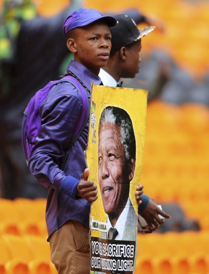 A man holds a placard at the First National Bank Stadium during the national memorial service for former South African President Nelson Mandela in Johannesburg December 10, 2013. World leaders from U.S. President Barack Obama to Cuba's Raul Castro joined thousands of South Africans to honor Nelson Mandela on Tuesday in a memorial that will celebrate his gift for uniting enemies across political and racial divides. (Siphiwe Sibeko/Reuters)