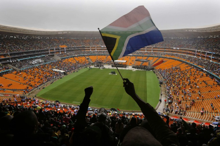 A man waves a South African flag during a memorial service for former South African President Nelson Mandela at the First National Bank (FNB) Stadium, also known as Soccer City, in Johannesburg December 10, 2013. World leaders from U.S. President Barack Obama to Cuba's Raul Castro joined thousands of South Africans to honour Mandela on Tuesday in a memorial that will celebrate his gift for uniting enemies across political and racial divides. (Yannis Behrakis/Reuters)