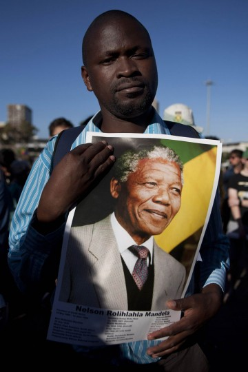 A man holds a poster of the late former President Nelson Mandela during an interfaith service held in front of the Town Hall on Grand Parade, Cape Town December 6, 2013. South African anti-apartheid hero Mandela died peacefully at home in Johannesburg at the age of 95 on Thursday after months fighting a lung infection, leaving his nation and the world in mourning for a man revered as a moral giant. (REUTERS/Mark Wessels)