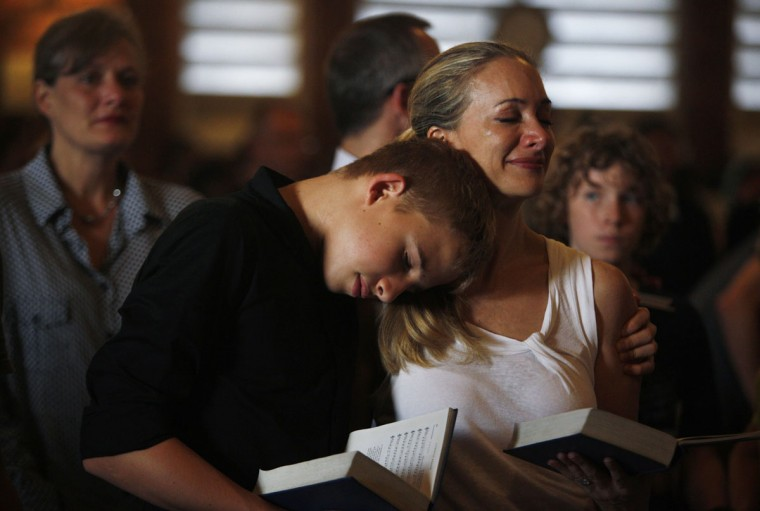 South African expatriate Janine Daniels is comforted by her son Liam, 15, as they sing during a memorial service for former South African President Nelson Mandela at St George Church in Singapore December 12, 2013. The anti-apartheid hero's death on December 5 at the age of 95 has brought an outpouring of grief and mourning, as well as celebration and thanksgiving for his life and achievements. (REUTERS/Edgar Su)