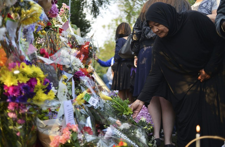 A woman offers flowers outside the house of former President Nelson Mandela in Johannesburg December 6, 2013. South African anti-apartheid hero Mandela died peacefully at home in Johannesburg at the age of 95 on Thursday after months fighting a lung infection, leaving his nation and the world in mourning for a man revered as a moral giant. (REUTERS/Mujahid Safodien)