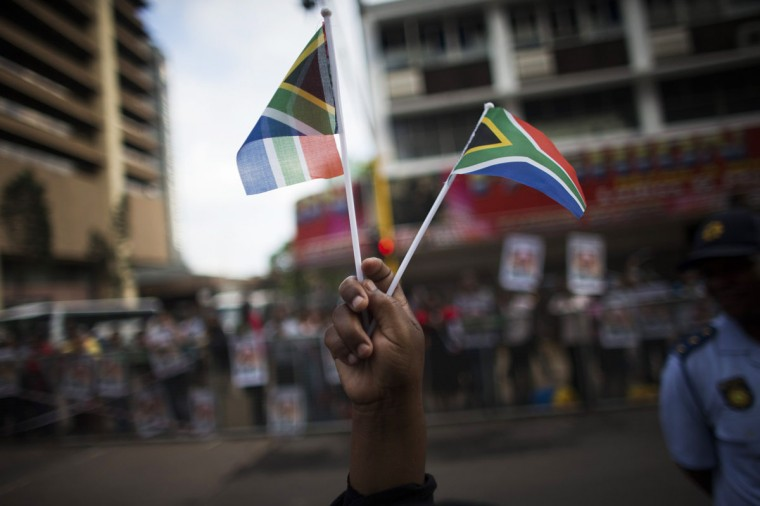 A woman holds flags as she waits for the cortege carrying the coffin of former South African President Nelson Mandela in the city center of Pretoria, as it travels on its way to the Union Buildings, December 12, 2013. (REUTERS/Ronen Zvulun)