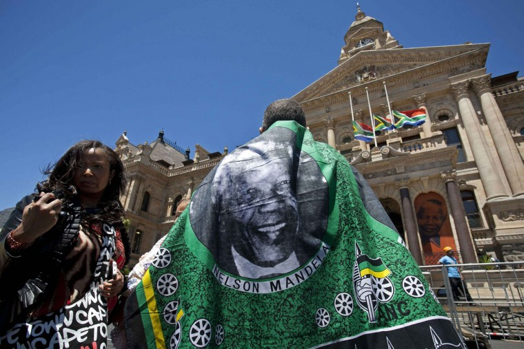 A man wearing a Nelson Mandela printed cloth stands in front of the Town Hall in Cape Town as he joins along with others to write condolences in a book for Mandela December 6, 2013. South African anti-apartheid hero Mandela died peacefully at home in Johannesburg at the age of 95 on Thursday after months fighting a lung infection, leaving his nation and the world in mourning for a man revered as a moral giant. (REUTERS/Mark Wessels)