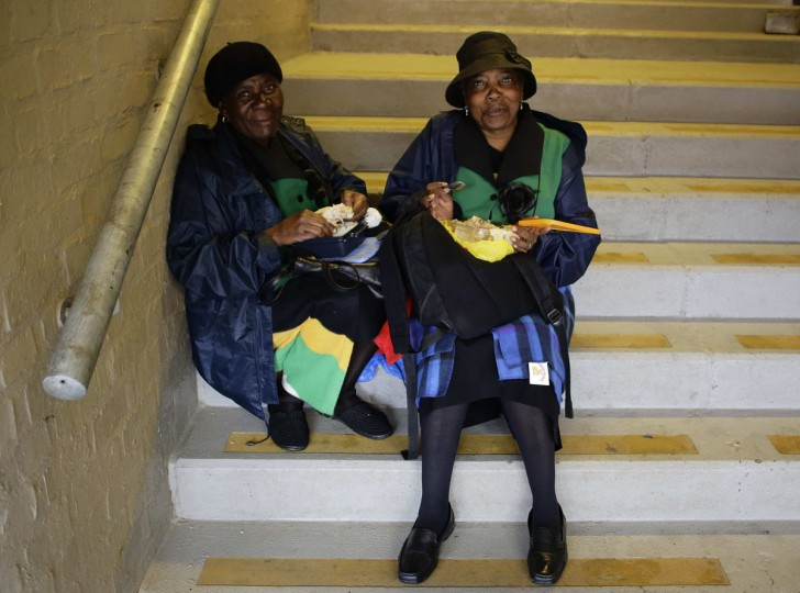 Two women eat their food whilst sitting on steps before a service for former South African President Nelson Mandela at the First National Bank Stadium, also known as Soccer City, in Johannesburg December 10, 2013. World leaders from U.S. President Barack Obama to Cuba's Raul Castro joined thousands of South Africans to honour Nelson Mandela on Tuesday in a memorial that will celebrate his gift for uniting enemies across political and racial divides. (Kevin Coombs/Reuters)