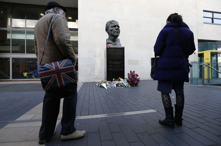 Two people look at flowers and tributes left for South Africa's former president Nelson Mandela near a statue of him at South Bank in London December 6, 2013. South African anti-apartheid hero Mandela died peacefully at home in Johannesburg at the age of 95 on Thursday after months fighting a lung infection, leaving his nation and the world in mourning for a man revered as a moral giant. (REUTERS/Suzanne Plunkett)