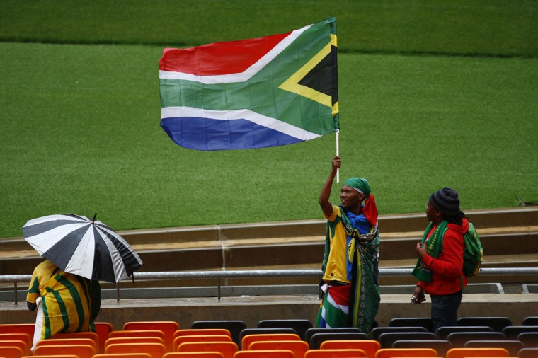 A man raises the South African national flag during the service for former South African President Nelson Mandela at the First National Bank Stadium in Johannesburg, December 10, 2013. World leaders from U.S. President Barack Obama to Cuba's Raul Castro joined thousands of South Africans to honor Nelson Mandela on Tuesday in a memorial that will celebrate his gift for uniting enemies across political and racial divides. (Kevin Coombs/Reuters)