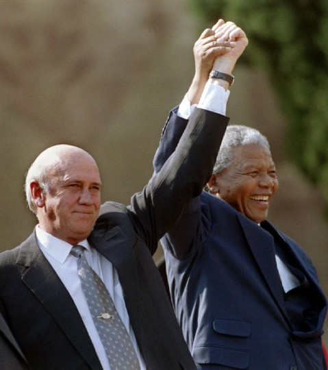 South African President Nelson Mandela (R) and Second Deputy President F.W. de Klerk hold their hands high as they address a huge crowd of people in front of the Union Building after the inauguration ceremony in Pretoria in this May 10, 1994 file photo. Mandela has passed away on December 5, 2013 at the age of 95. (Juda Ngwenya/REUTERS files)
