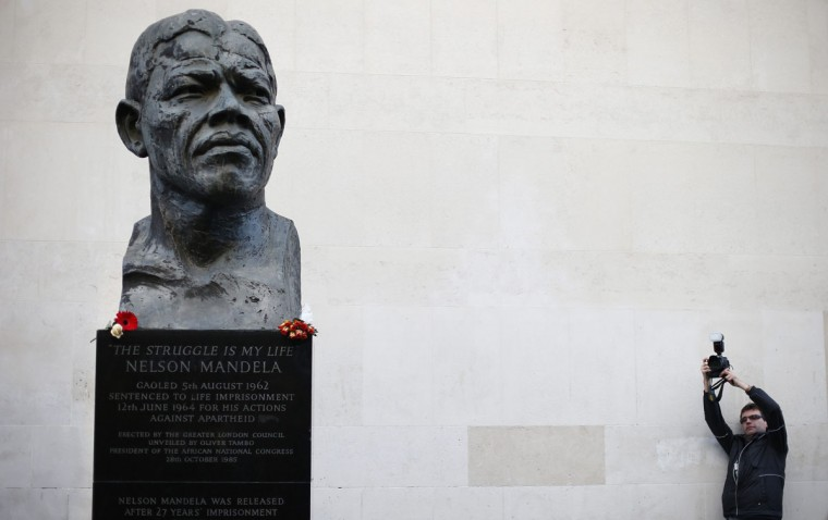 A man takes a photograph of a statue of South Africa's former president Nelson Mandela at South Bank in London December 6, 2013. South African anti-apartheid hero Mandela died peacefully at home in Johannesburg at the age of 95 on Thursday after months fighting a lung infection, leaving his nation and the world in mourning for a man revered as a moral giant. (REUTERS/Suzanne Plunkett)