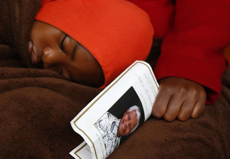 A boy sleeps on his mother's lap at the First National Bank Stadium, also known as Soccer City, ahead of former South African President's Nelson Mandela's national memorial service in Johannesburg December 10, 2013. World leaders from U.S. President Barack Obama to Cuba's Raul Castro joined thousands of South Africans to honor Nelson Mandela on Tuesday in a memorial that will celebrate his gift for bringing enemies together across political and racial divides. (Yves Herman/Reuters)