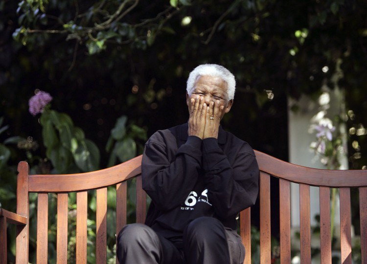 Nelson Mandela laughs with journalists and performers participating in the second 46664 concert near the small Western Cape province town of George in this March 18, 2005 file photo. Mandela has passed away on December 5, 2013 at the age of 95. (Mike Hutchings/REUTERS files)