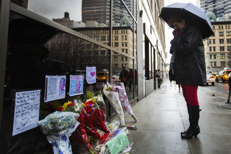 A woman wipes tears from her face as she stops to look at a memorial for the late Nelson Mandela outside the office of the South African Consulate General in New York, December 6, 2013. South African anti-apartheid hero Mandela died peacefully at home in Johannesburg at the age of 95 on Thursday after months fighting a lung infection, leaving his nation and the world in mourning for a man revered as a moral giant. (REUTERS/Lucas Jackson)