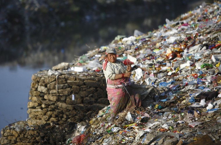 A woman searches for recyclable waste at a dump site on the banks of Bagmati River in Kathmandu December 23, 2013. According to one of the workers from the site, they each earn about $5 a day. (Navesh Chitrakar/Reuters)