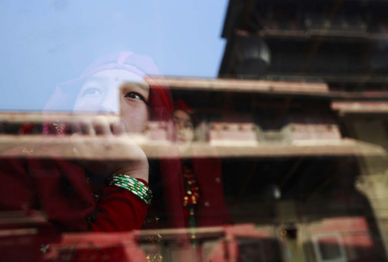 A Gurung girl wearing a traditional costume watches a passing New Year parade from inside a cafe in Kathmandu December 30, 2013. The Gurung community in Nepal celebrates their Tamu Lhosar or Losar (New Year) with a feast and various cultural programs to usher in the year of the horse. (Navesh Chitrakar/Reuters)